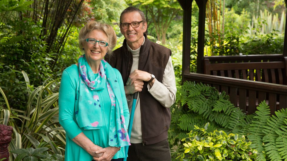 Marie and Tony Newton stood in their garden with lots of greenery surrounding them