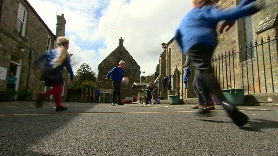Primary school children playing football