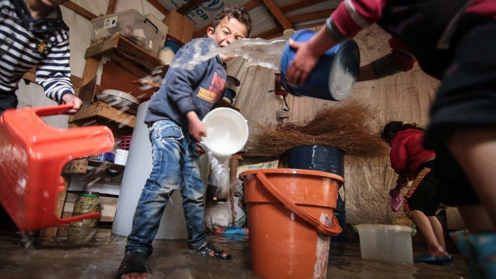 طفل يساعد بإزالة المياه من الخيمة التي طافت في فصل الشتاء (يناير 2018) في مخيم في منطقة البقاع.