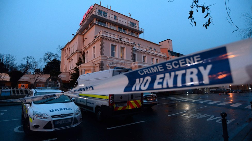Police officers and vehicles at the scene of the shooting at Dublin's Regency Hotel
