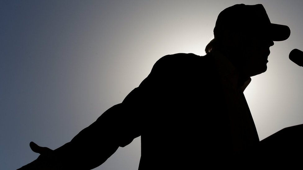 Donald Trump - in silhouette - speaks at a rally