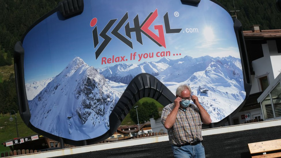 A man removes a protective face mask after photographing himself in front of an advertisement in the shape of ski goggles for the Ischgl ski resort