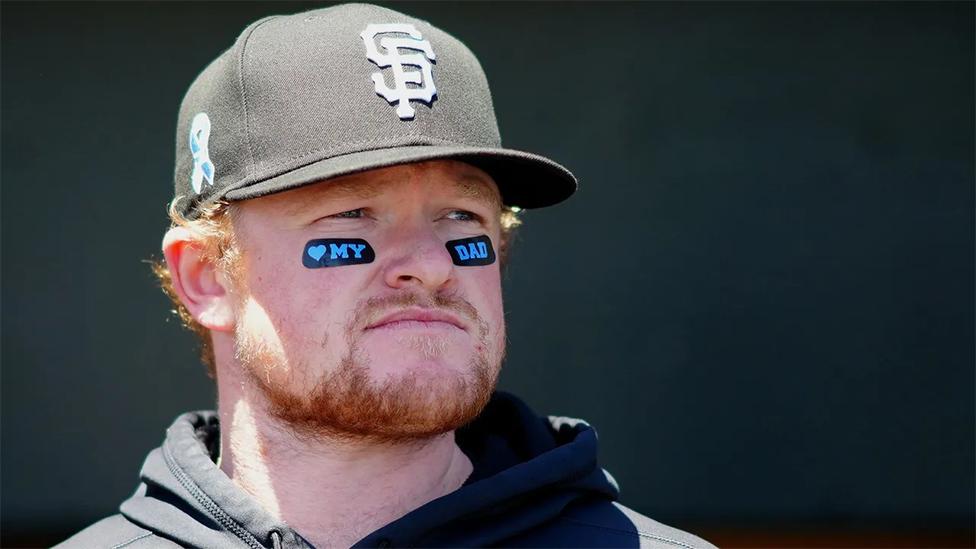 """Un aficionado del baseball con unos dibujos en su rostro que dicen: """"amo a mi padre""""."""