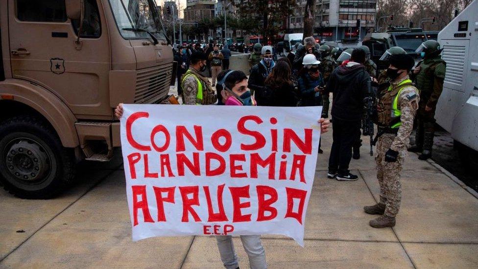 Manifestante de máscara segura cartaz que diz: 'Com ou sem pandemia, aprovo!'