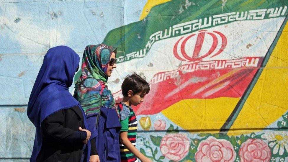 Dos mujeres y un niño caminan delante de un mural con la bandera iraní.