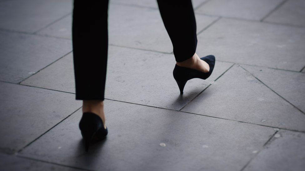 Woman's feet avoiding crack on pavement