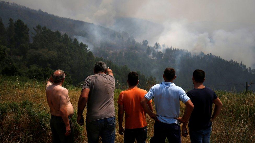 Homens observam incêndio em Portugal à distância