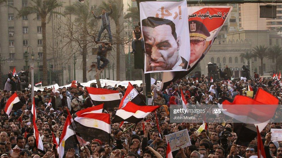 متظاهرون في ميدان التحرير، وسط القاهرة، يرفعون لافتة تطالب مبارك بالرحيل عن السلطة في أثناء ثورة 25 يناير 2011