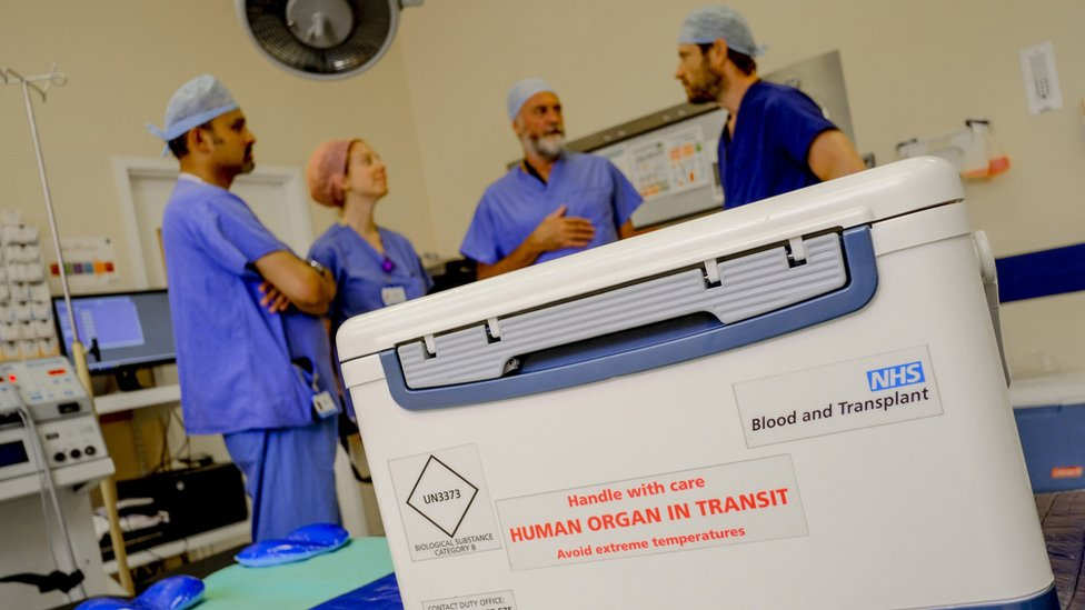 An organ in transit in a hospital room filled with doctors