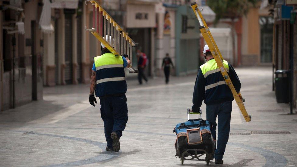 Dos obreros de la construcción caminan por una calle de Madrid.