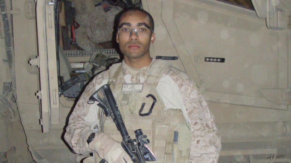 Kyle Bibby holding military gear, gun