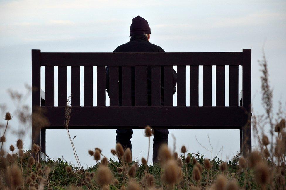Un hombre mayor sentado en un banco