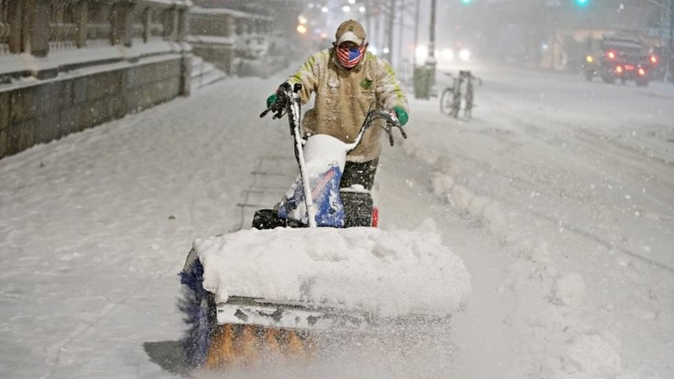 """A man clears snow as snow falls near Bryant park during a Nor""""easter, during the coronavirus disease (COVID-19) pandemic in the Manhattan borough of New York City, New York, US on 16 December 2020"""