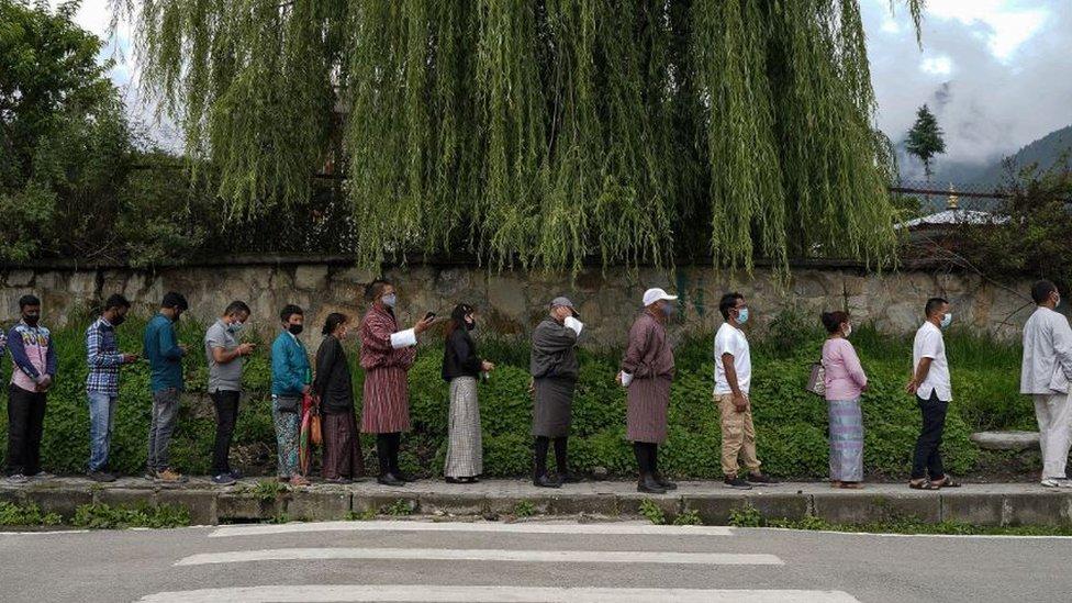 Pessoas fazem fila para se registrar e serem inoculadas com vacina contra Covid-19 em um centro temporário de vacinação em Thimpu