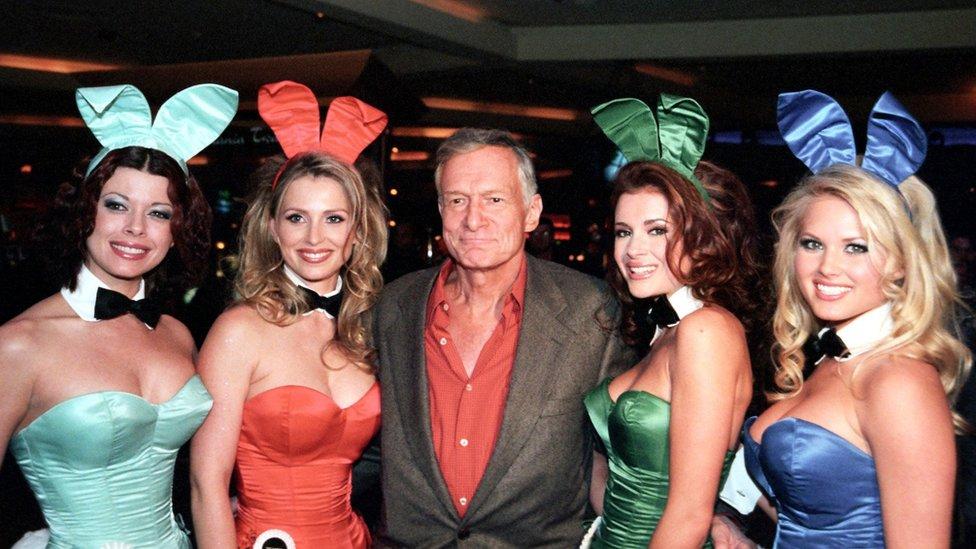 Hugh Hefner with four women in Playboy uniforms