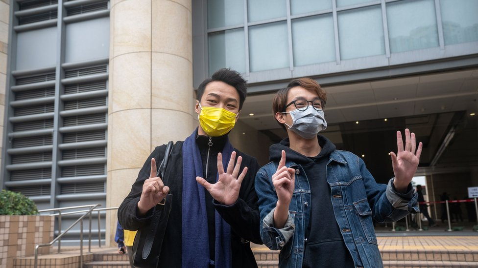 2020/12/17: Pro-democracy activists Jimmy Sham Tsz-kit (L) and Figo Chan (R) make gestures outside of West Kowloon Courts before they attend court hearing for their charges of illegal assembly from a protest on July 1 this year.