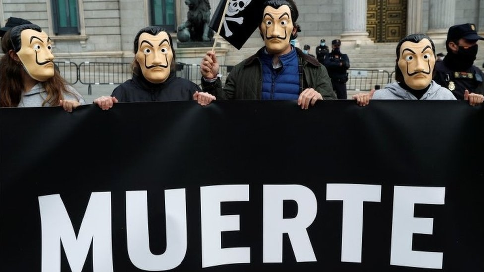 """Protesters outside Spain's parliament in Madrid show part of a banner with the word """"death"""". Photo: 17 December 2020"""