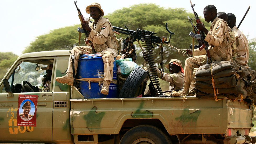 Rapid Support Forces holding guns while driving in the back of a pick-up truck