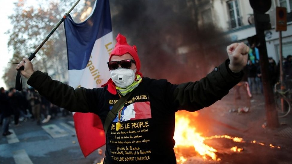 A protester in Paris holds France's national flag in front of burning fire. Photo: 28 November 2020