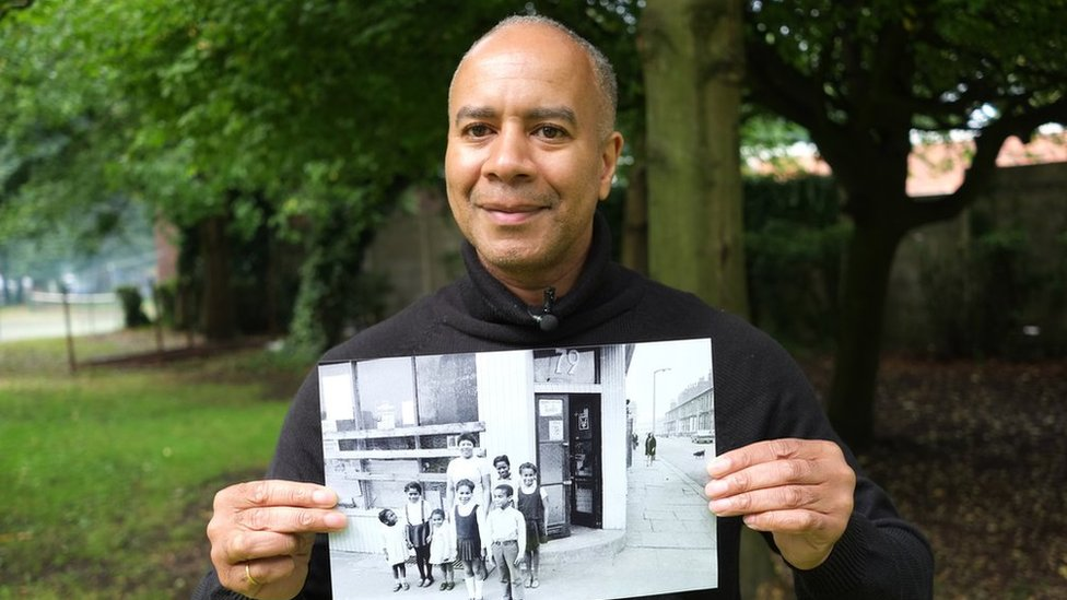 man poses with picture of when he was young