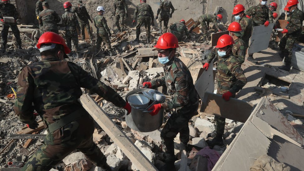 عمال الإنقاذ يرفعون أنقاض مبنى سكني مدمر في مدينة كنجة الأذرية بحثا عن ناجين