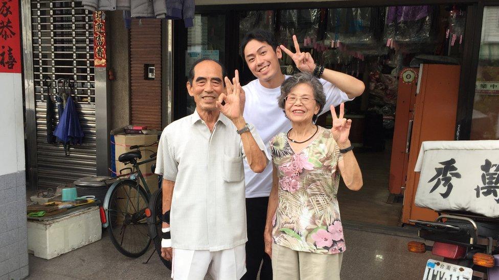 Chang Wan-ji, Reef Chang and Hsiu Sho-er outside their laundry shop