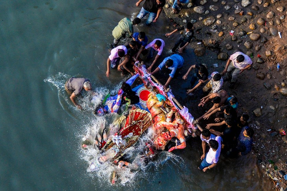 Hindu devotees submerge a clay idol of the Hindu goddess Durga on the final day of the Durga Puja festival in Dhaka on 8 October 2018.