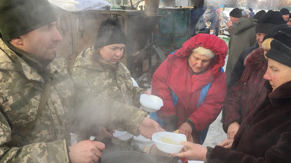 Ukrainian soldiers hand out hot stew to queues of people at temporary aid camp in Avdiivka