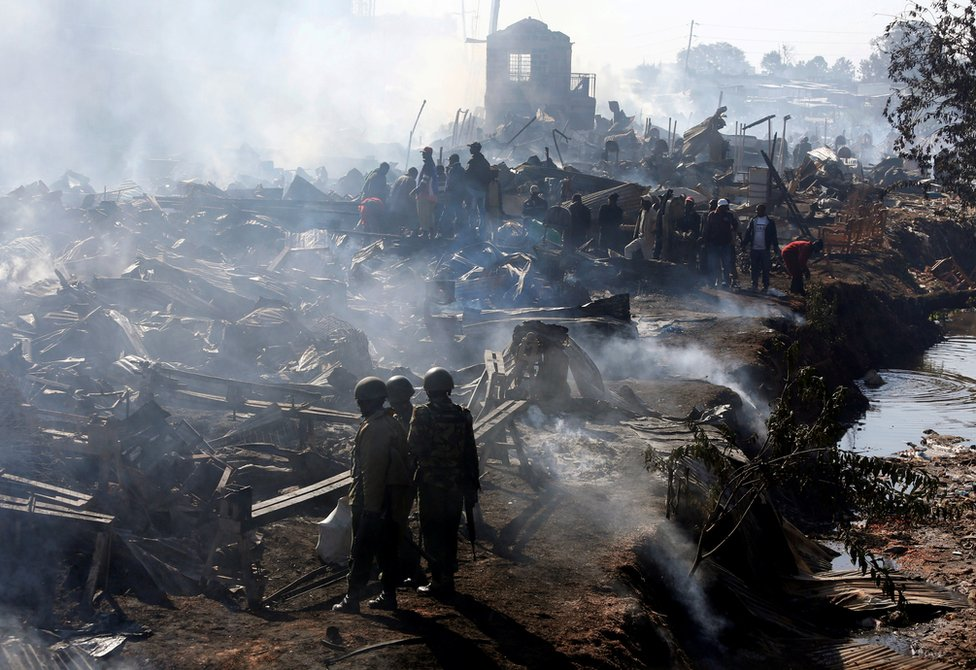 Traders and riot police are seen at the smouldering scene of fire that gutted down the timber dealership of the Gikomba market and nearby homes in central Nairobi, Kenya June 28, 2018