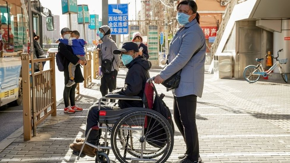 Chinese people wear protective masks as they wait for the bus