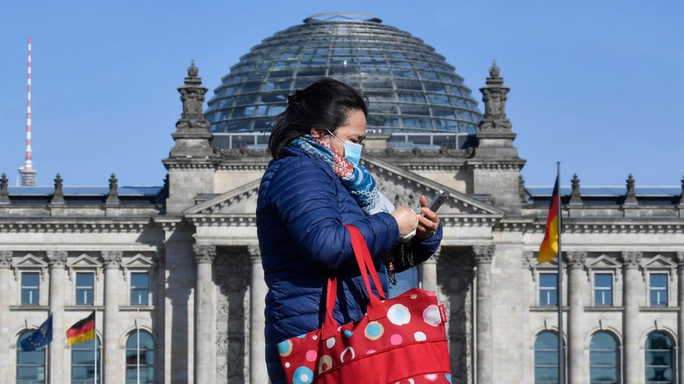 Woman walks past Reichstag wearing a mask