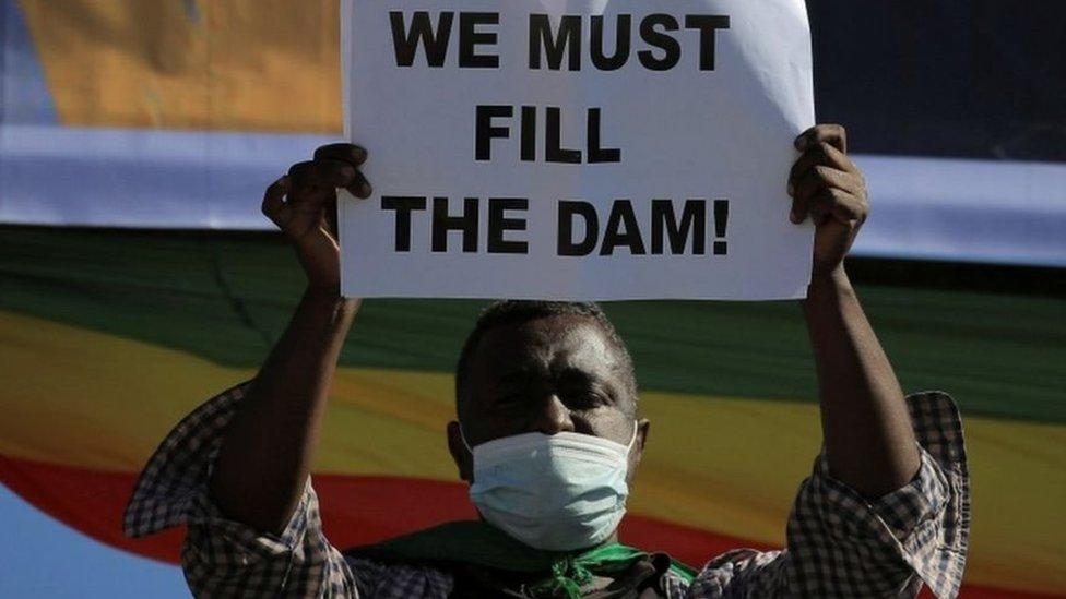 """إثيوبي يرفع لافتة تقول """"يجب ملء السد"""""""