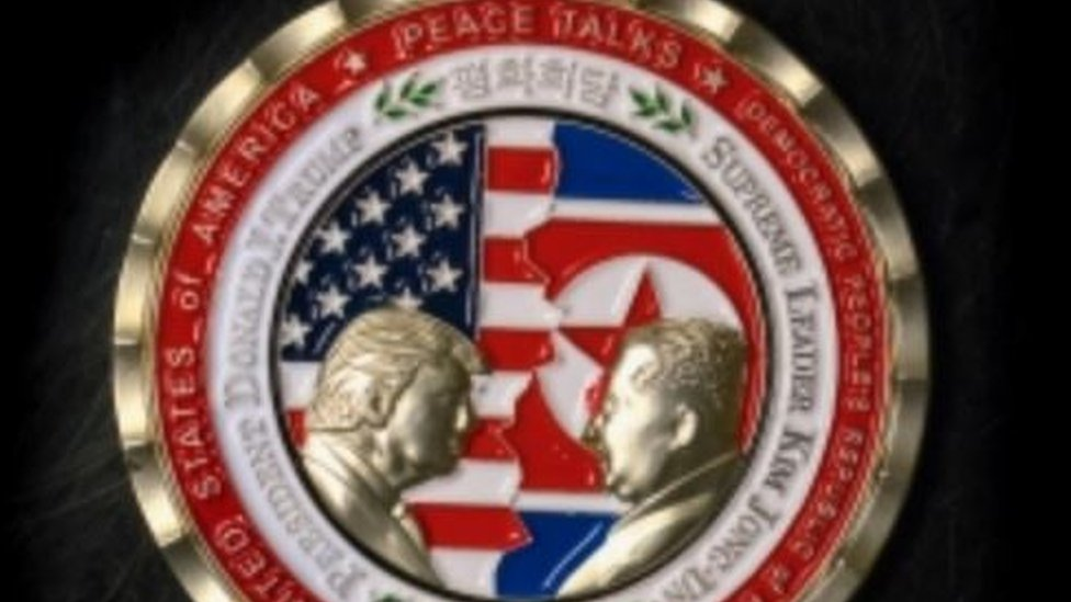 """A commemorative coin issued by the White House, depicting Mr Trump and Mr Kim facing each other in front of a background of US and North Korean flags. The words """"Peace Talks"""" are emblazoned at the top of the front of the coin with the date """"2018"""" beneath."""