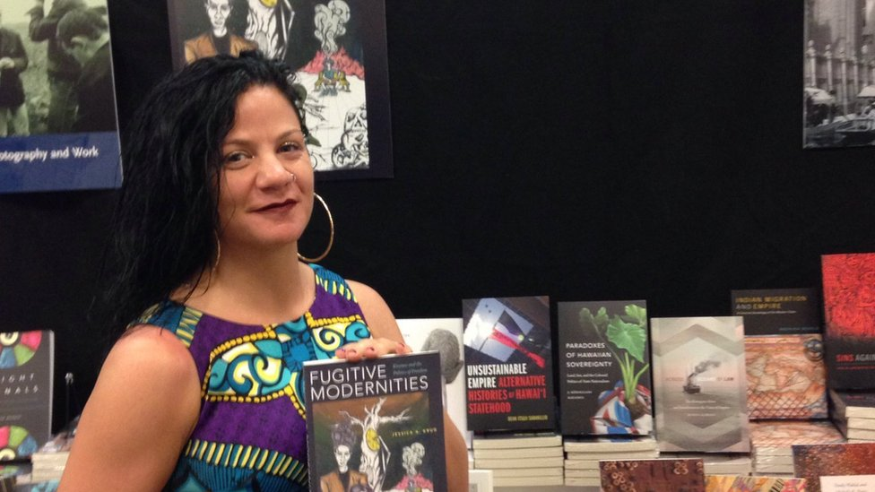 Jessica Krug poses with her book Fugitive Modernities in 2019