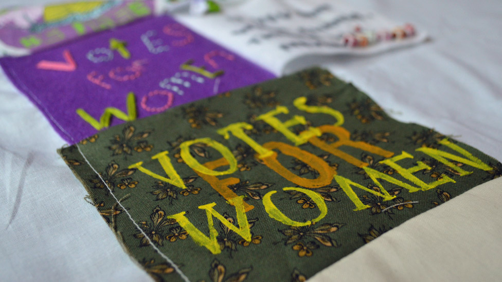 """""""Votes For Women"""" patch on Girl Gang Manchester's banner"""