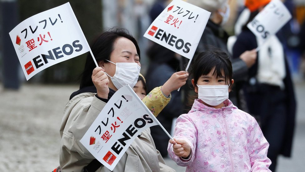 Spectators wearing face masks wait for the arrival of the Tokyo 2020 Olympic torch relay, amid the coronavirus disease (COVID-19) pandemic, on the second day of the relay in Fukushima, Japan March 26, 2021.