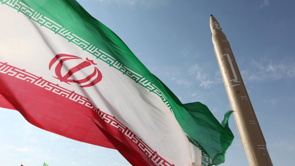 Iranian flag flying at an undisclosed location in Iran next to a surface-to-surface Qiam-1 missile (20 August 2010)