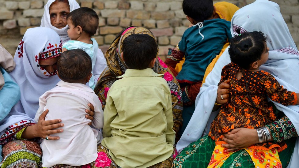 Parents nervously watch over their children as they jostle in line to be tested for HIV in a village near Pakistan's Larkana amid a sudden outbreak among its young