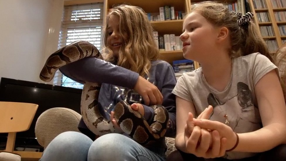 Girl holding snake at a party