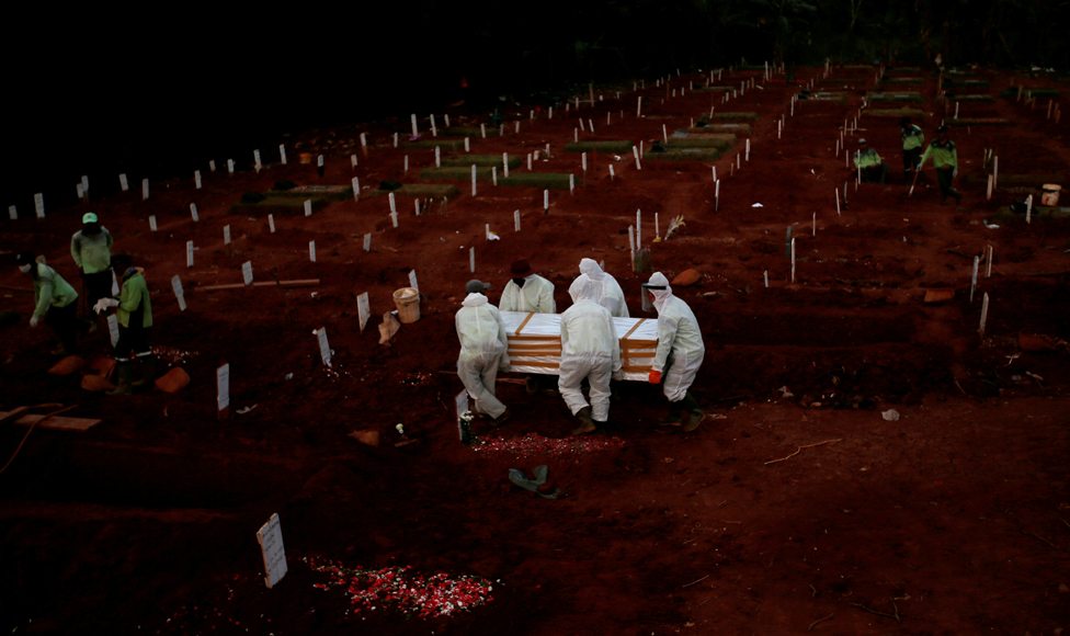 Workers carry a coffin in a cemetery complex for coronavirus victims in Jakarta, Indonesia, 22 April 2020