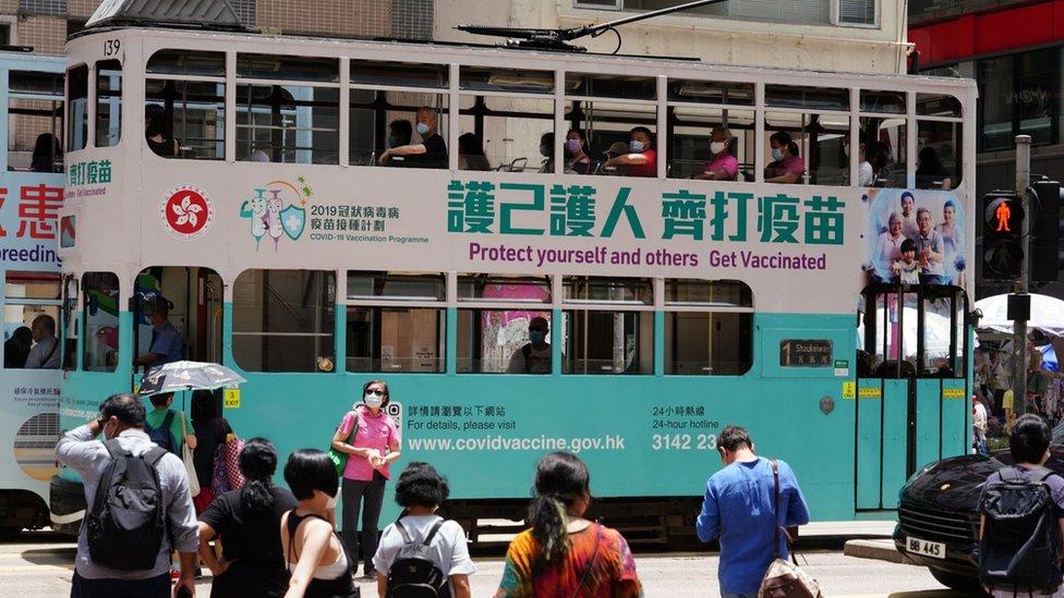 一輛印有「護己護人齊打疫苗」車身廣告的電車駛過香港灣仔街頭(中新社圖片19/5/2021)