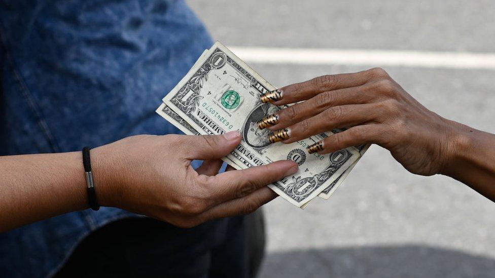 La mano de una mujer pagando en dólares