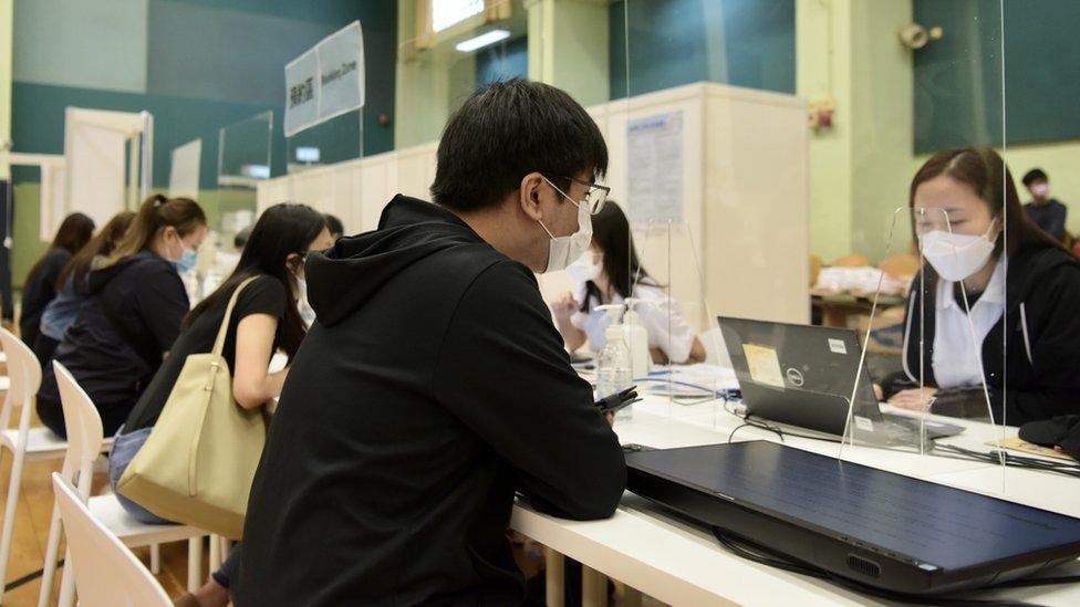 香港某社區疫苗接種中心內工作人員為已預約接種市民核對資料(中新社圖片13/3/2021)