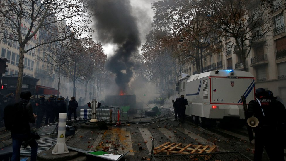 """rench riot police stand guard near a barricade during clashes with protesters wearing yellow vests, a symbol of a French drivers"""" protest against higher diesel taxes, at the Place de l""""Etoile in Paris, France, December 1, 2018"""
