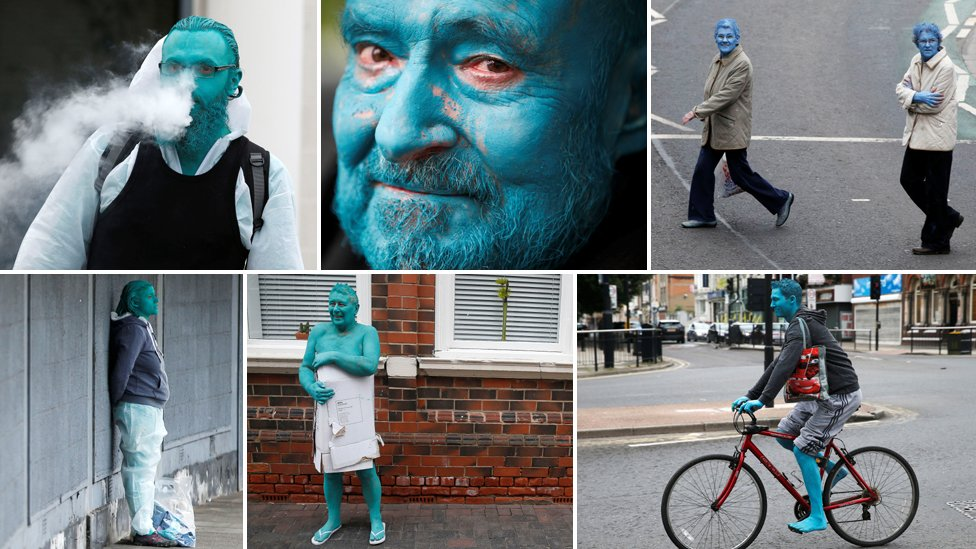 Nude people painted blue pose