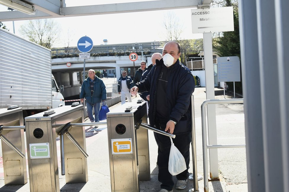 A man walks through a turnstile whilst wearing a face mask