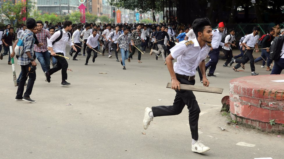 Students run back during clashes while protesting over recent traffic accidents that killed a boy and a girl, in Dhaka.