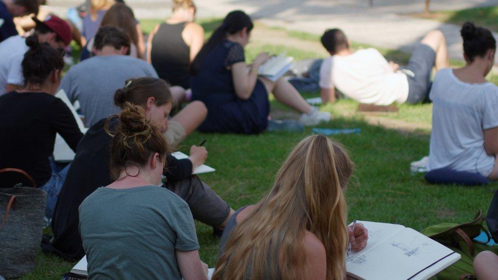 Estudiantes universitarios leyendo sobre el césped.