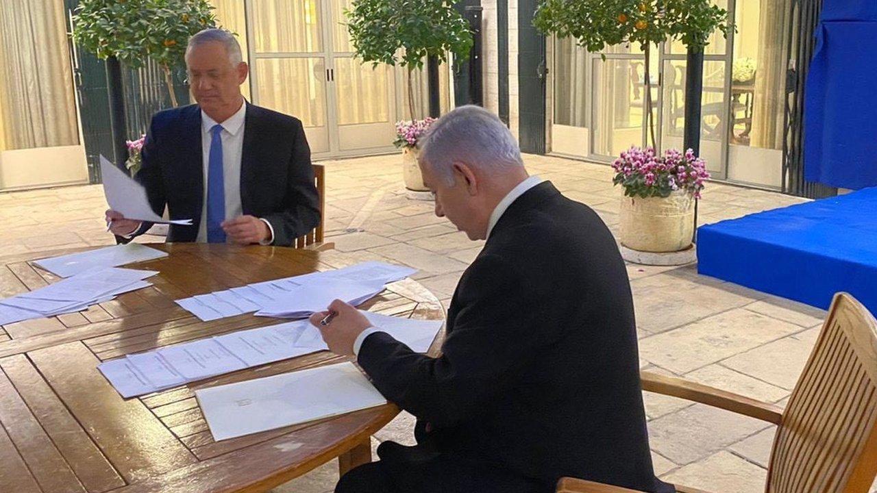 Benny Gantz (left) and Benjamin Netanyahu (right) sign a coalition deal in Jerusalem on 20 April 2020