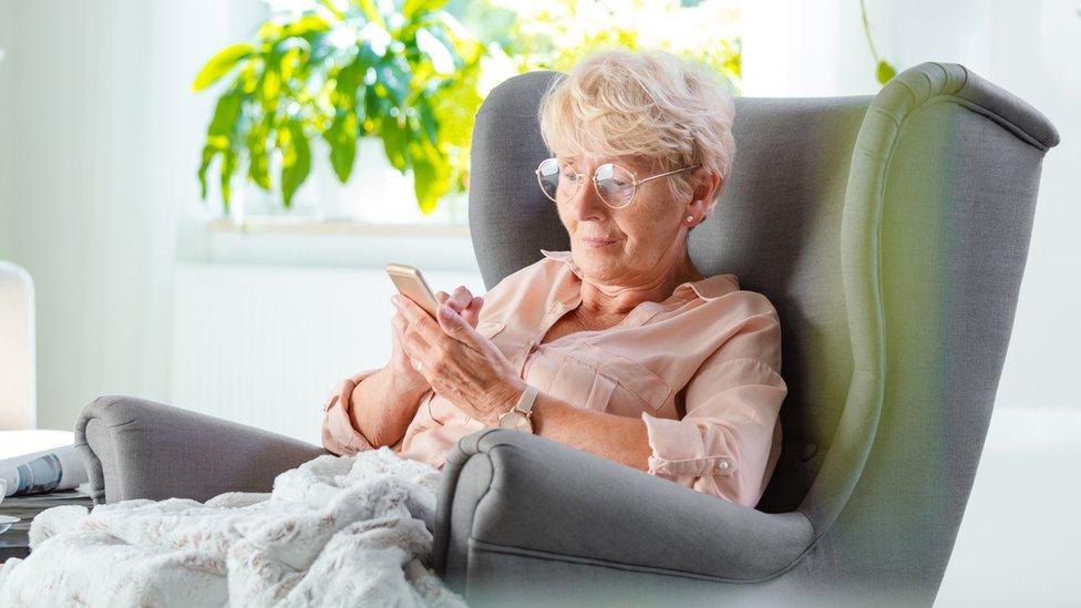Persona mayor que mira su teléfono